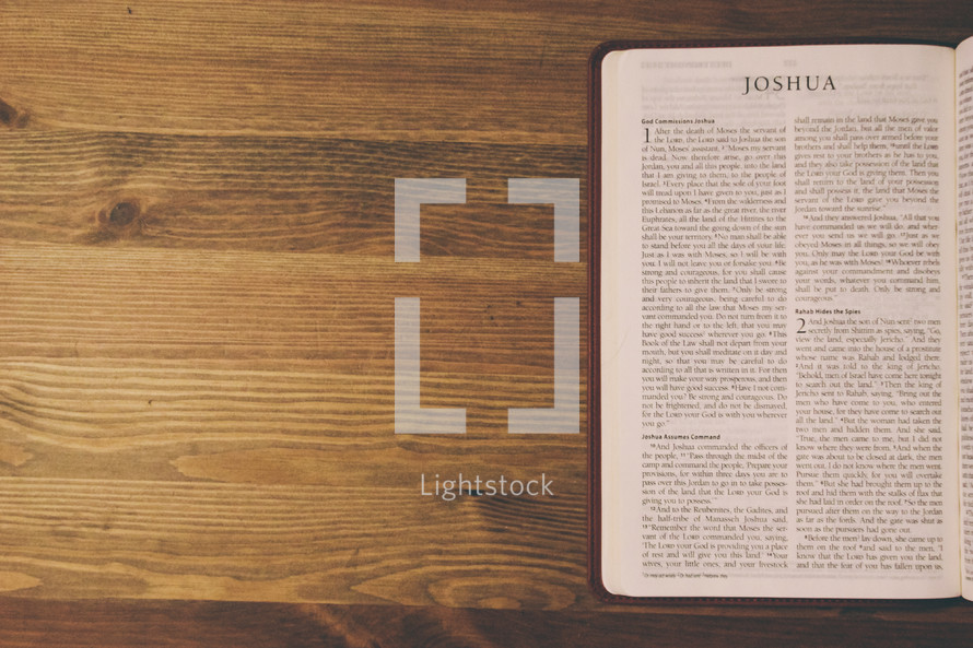 Bible on a wooden table open to the book of Joshua.