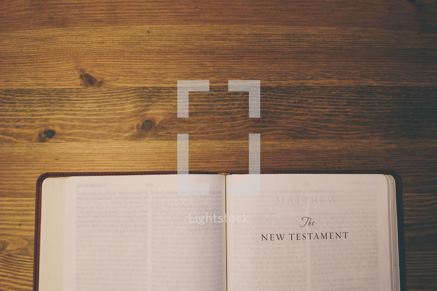 Bible on a wooden table open to the New Testament.