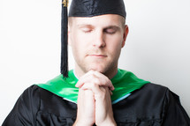 Graduate with hands clasped in prayer.