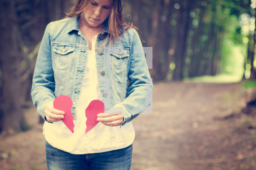 Woman standing on a trail outside holding the pieces of a broken heart.