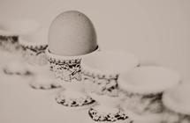 Brown, speckled Easter egg in vintage egg dishes.