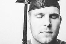Graduate with eyes closed in prayer.