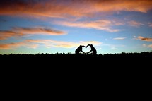 A silhouette of two people making a big heart with their arms, with clouds lit by a sunset behind them.