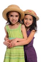 Two little girls wearing hats.