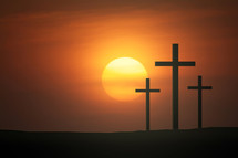 three crosses against a red/orange sky a sunset