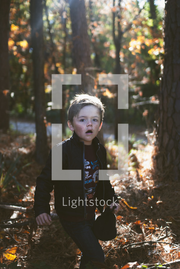 young boy walking through a forest