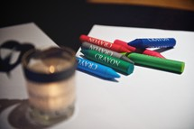 Crayons and paper on a table with a candle.
