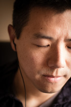 man listening to music with earbuds in