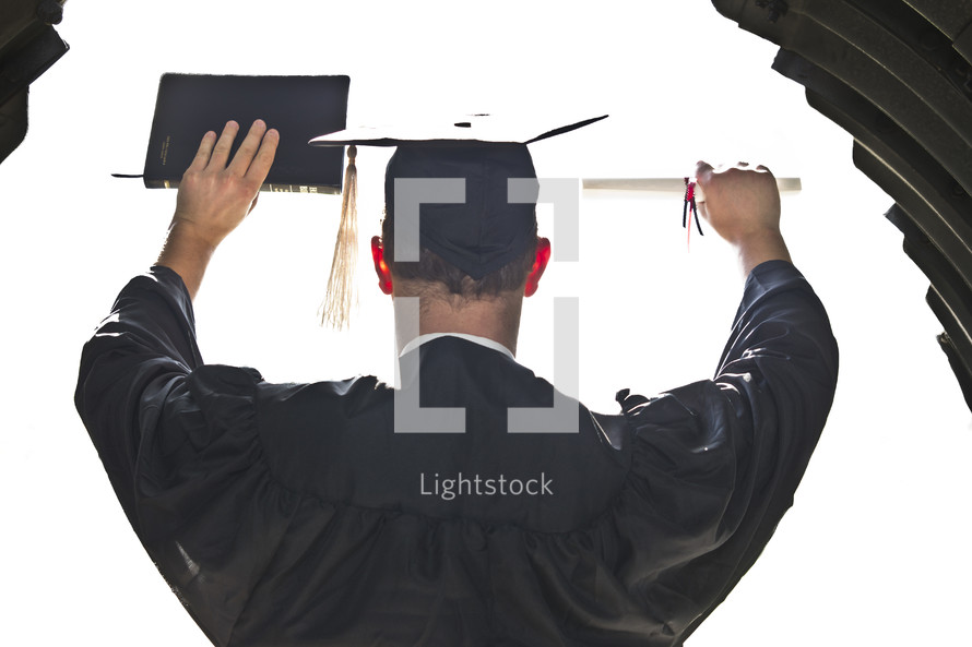 graduate holding up his diploma and a Bible