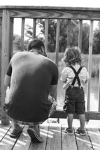 Father and son on a wooden deck overlooking a pond.