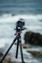 A video camera on a tripod pointed at the ocean.