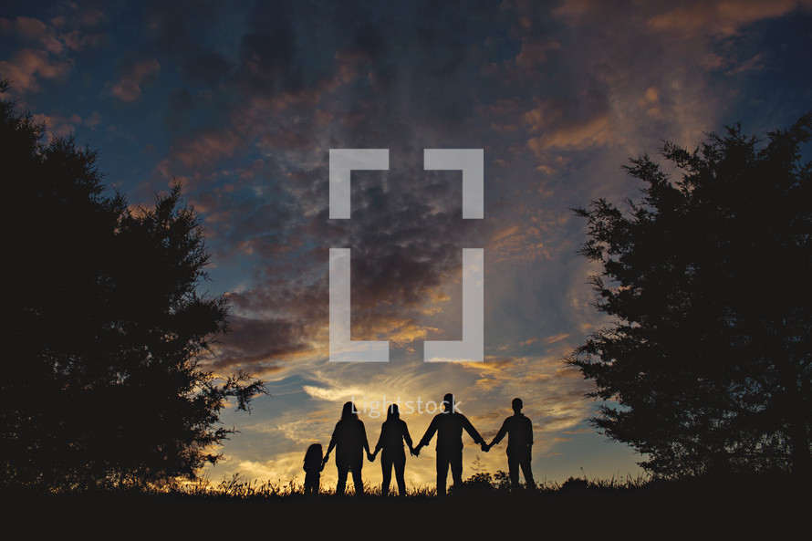 silhouette of a family standing outdoors holding hands under an evening sky
