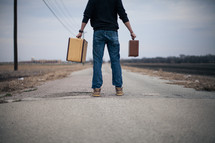 man holding out suitcases standing in the middle of a road