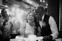 A bride and groom laughing together.