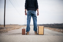 man standing looking down a road standing next to suitcases