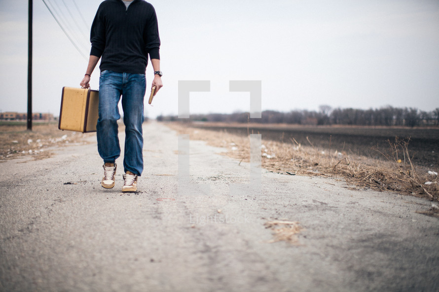 man carrying a suitcase walking down the middle of a road