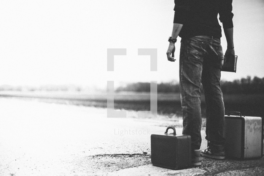 man standing next to a suitcase holding a Bible looking down a road