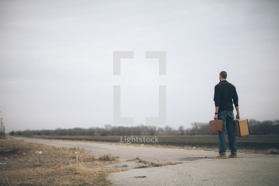 man walking down the middle of a road carrying suitcases