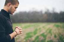 man standing in a field with his head bowed in prayer