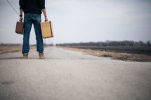 man holding suitcases looking down a long road