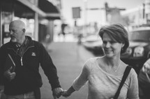 a couple holding hands walking down a sidewalk