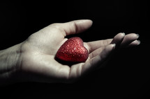 a red heart in a cupped hand
