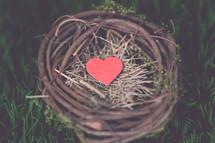 A wooden heart in a bird's nest