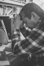 a man sitting at a desk praying and reading a Bible