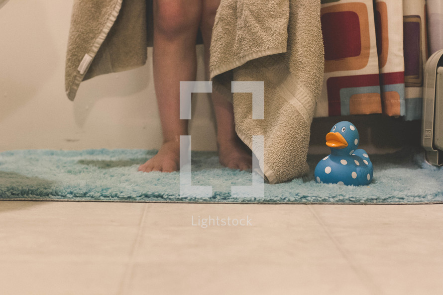 Child's legs standing on a rug with a towel and a rubber duck.