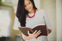 woman standing reading a Bible