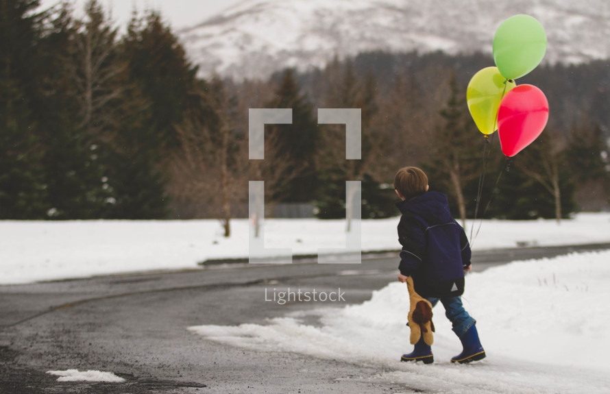 boy child walking in the snow holding a teddy bear and balloons