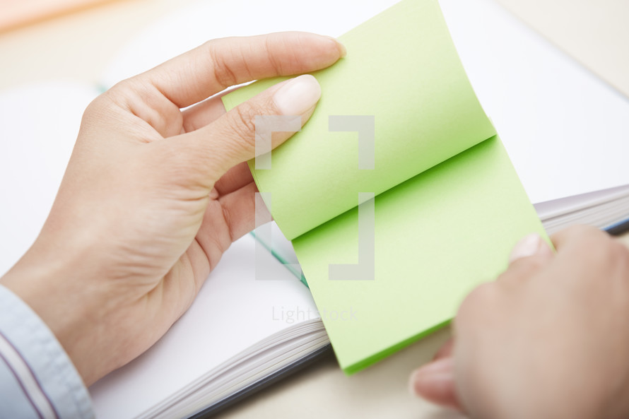 a woman holding a pad of sticky notes
