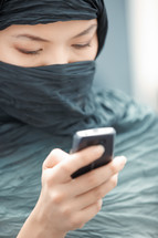 veiled woman checking her cellphone