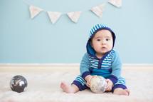 infant boy holding a globe ball