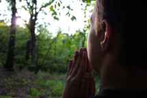 boy praying in a forest