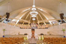 man in prayer in an empty church