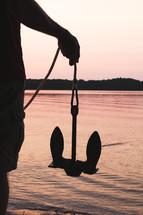 a man holding an anchor at sunset
