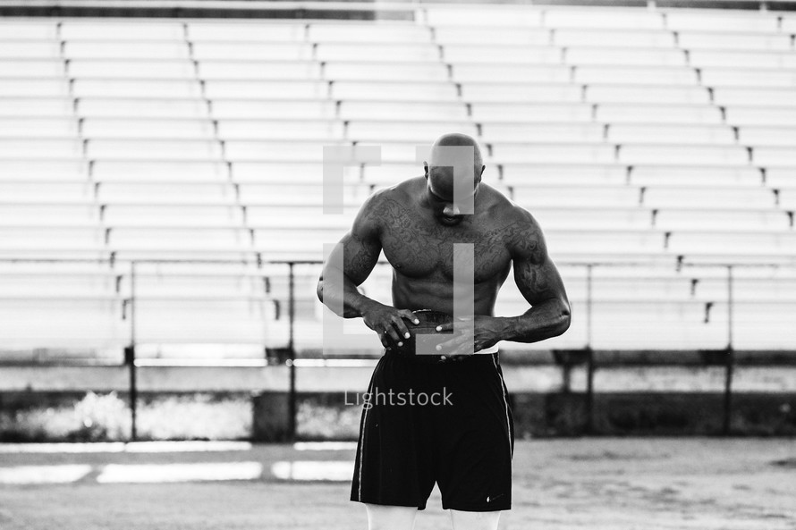a shirtless man with tattoos standing on a football field