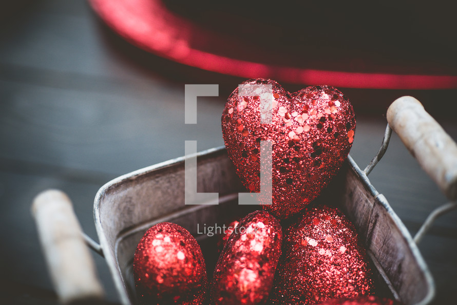 red sparkly hearts in a bucket