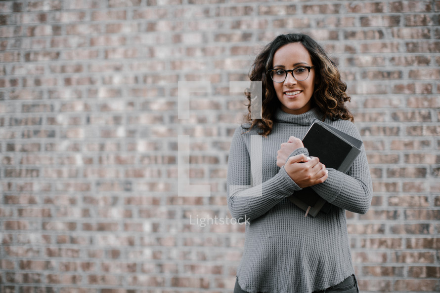 a young woman holding a stack of books standing in front of a brick wall