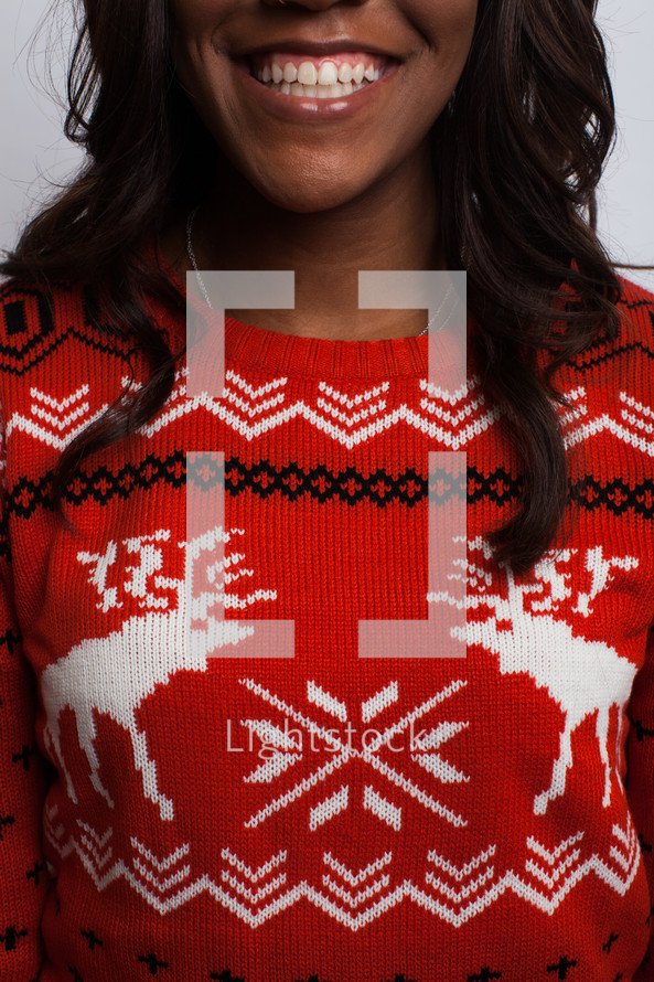 smiling woman in an ugly Christmas sweater