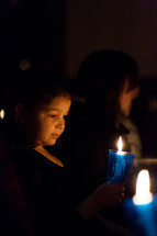 a child holding a candle at a Christmas Eve Candlelight service