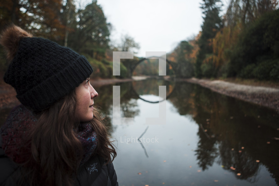 a woman sitting in front of a round bridge
