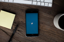 a workspace with Twitter app on a cellphone screen