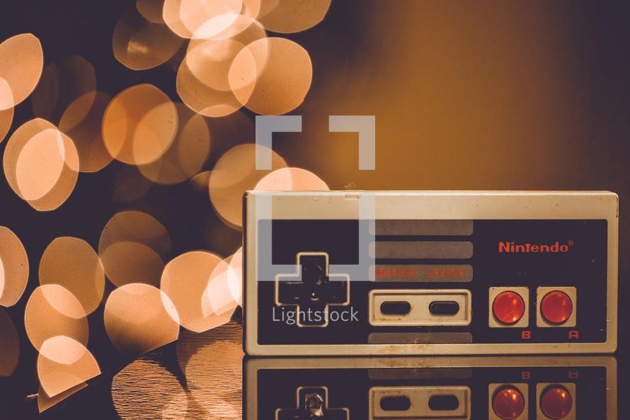 vintage nintendo remote control and bokeh lights