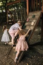 children climbing a climbing wall