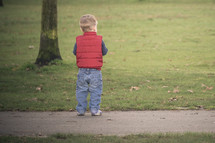 toddler boy in a vest standing on a sidewalk