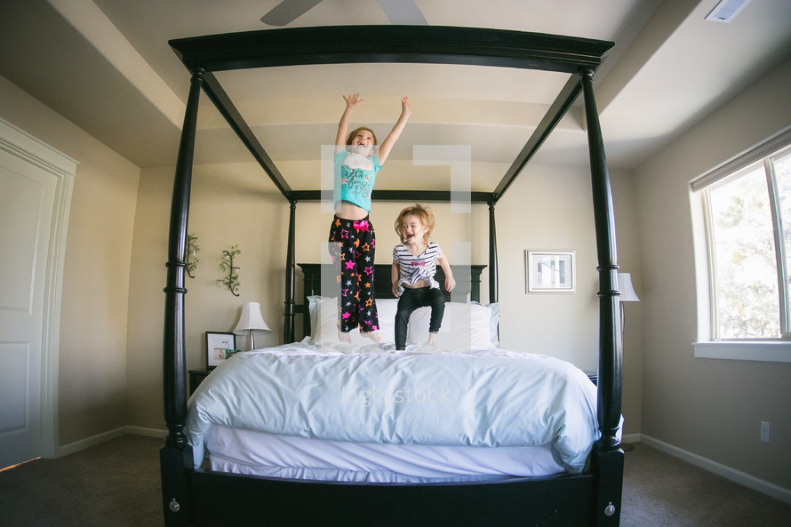 sisters jumping on a bed