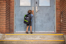 a boy with a backpack standing in front of school doors