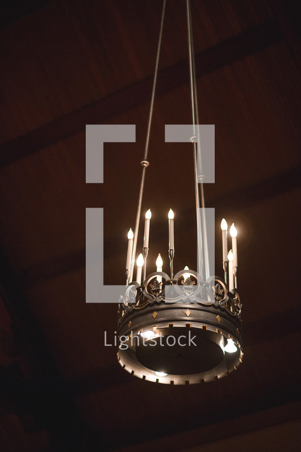 A candelabra hanging from a wooden ceiling.